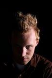 Schlechter schauender Mann mit halbem Gesicht im Schatten Stockbilder