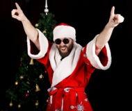 Schlechtes rastoman Santa Claus lächelt und Spaßtanzen auf dem Hintergrund des Weihnachtsbaums lizenzfreies stockbild