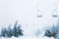 Schlechtes Wetter im Skiort hebt über den Wald an Stockbild