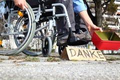 Schlechtes wheelchairuser, das um Geld bittet stockfotografie