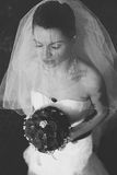 Schleier bedeckt eine Braut, die mit geschlossenen Augen und einem Hochzeit bouq steht Lizenzfreie Stockfotos