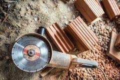 Schleifer benutzt auf Baustelle für den Schnitt von Ziegelsteinen, Rückstand Werkzeuge und Ziegelsteine auf Neubaustandort Stockbild