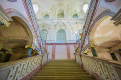 Schleissheim, Germany - July 30, 2015: Ancient staircase inside palace building from down looking up, beautiful royal decorations. On wall stock photography