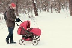Schlendernder Kinderwagen des jungen Mannes mit Baby im Winterpark Lizenzfreie Stockfotografie