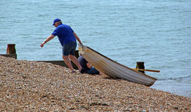 Schleppen des Ruderboots auf Strand Stockfotografie