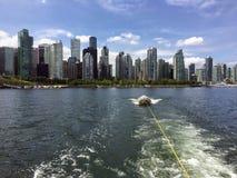 Schleppen eines kleinen Bootes oder des Schlauchboots an einem Sommertag mit den Skylinen O lizenzfreie stockfotografie