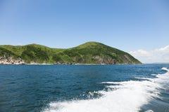 Schleppen Sie auf Meerwasseroberfläche hinter Boot gegen den Hintergrund des hügeligen Geländes Stockfotos