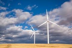 Schleppen Sie durch Feld nahe bei zwei Windmühlen in Washington Stockfoto