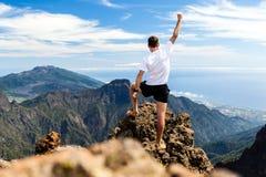 Schleppen Sie Läufererfolg, den Mann, der in Berge läuft Stockbild
