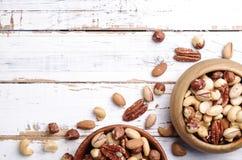 Schleppen Sie Mischung mit verschiedenen Arten von Nüssen in der braunen hölzernen Schüssel auf verkratztem weißem Holztischhinte Stockbilder