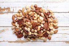 Schleppen Sie Mischung mit verschiedenen Arten von Nüssen in der braunen hölzernen Schüssel auf verkratztem weißem Holztischhinte Stockfotos