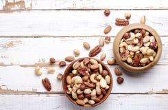 Schleppen Sie Mischung mit verschiedenen Arten von Nüssen in der braunen hölzernen Schüssel auf verkratztem weißem Holztischhinte stockfoto