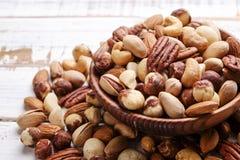 Schleppen Sie Mischung mit verschiedenen Arten von Nüssen in der braunen hölzernen Schüssel auf verkratztem weißem Holztischhinte lizenzfreies stockfoto
