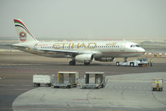 Schleppenflugzeuge Airbus A320-232 (A6-EIR) Etihad Airways im Fluggastterminal Abu Dhabi Airport Lizenzfreie Stockfotos