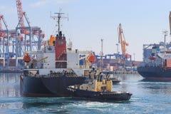 Schlepper am Bogen des Frachtschiffs, das Schiff unterstützend, um im Seehafen zu manövrieren lizenzfreie stockfotos