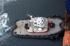 Schlepper, der auf ein Containerschiff drückt Lizenzfreie Stockfotografie