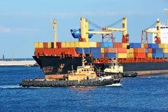 Schlepper, der BehälterFrachtschiff unterstützt Lizenzfreies Stockbild