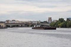 Schlepper, der einen schweren Lastkahn auf dem Fluss drückt stockfotos