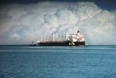 Schlepper drücken großes Schiff zum Meer Stockbilder