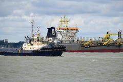 Schlepper führen heraus ein Containerschiff vom Hafen von Felixstowe Großbritannien stockfotografie