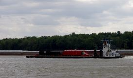 Schlepperboot drückt Ausrüstungslastkahn auf Fluss lizenzfreies stockbild