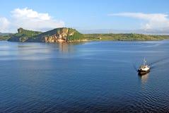 Schlepperboot nahe einer szenischen Küstenlinie Stockfotos