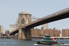 Schlepperboot unter Brooklyn-Brücke Stockfotos