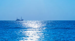 Schleppnetzfischerfischen in Meer bei Sonnenuntergang Stockbilder