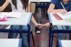 Schüler, der dem Mädchen Spickzettel am Schreibtisch führt Lizenzfreie Stockfotografie