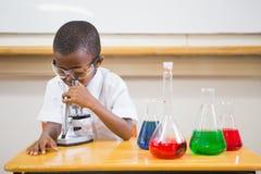 Schüler, der durch Mikroskop schaut Stockfotografie