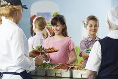 Schüler, die mit dem gesunden Mittagessen in der Schulkantine gedient werden Lizenzfreie Stockfotografie
