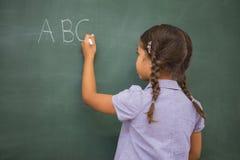 Schülerschreibensbuchstaben auf einer Tafel Stockfotos