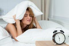 Schläfrige Frau, die versucht, sich unter dem Kissen zu verstecken Lizenzfreie Stockfotografie