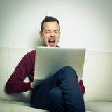 Schläfriger junger Mann, der auf einem Sofa sitzt und versucht, etwas Arbeit zu erhalten Lizenzfreies Stockbild