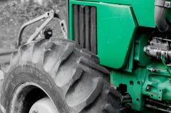 Schließen Sie auf einem grünen Traktor, in dem Sie die Haube, die Maschine und großen die Traktorreifen sehen können Lizenzfreie Stockfotografie