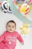 Schließen Sie bis zu einem netten Baby, das oben zu seinen Spielwaren in seiner Krippe schaut Stockfotos