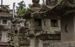 Schließen Sie bis zu vielen verschiedenen Steinlaternen auf dem Weg zu einem buddhistischen Tempel in Japan Tempel Higo Honmyo, P lizenzfreies stockfoto