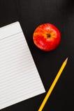 Schließen Sie bis zur leeren gezeichneten Seite des Notizbuches mit Apple und gelbem Bleistift Stockfotos