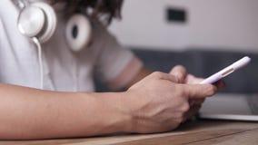 Schließen Sie extrem von einem jungen Mädchen im weißen Hemd, das durch die Tabelle mit Kopfhörern auf ihrem Hals sitzt In Verbin stock video