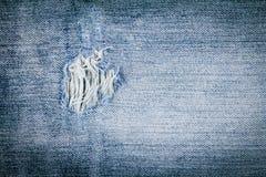 Schließen Sie herauf alte blaue Baumwollstoffbeschaffenheit mit heftigem Loch Lizenzfreie Stockbilder