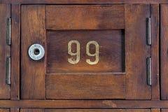 Schließen Sie herauf alten hölzernen Briefkasten mit Nr. 99 Stockfoto