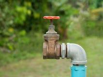 Schließen Sie herauf altes Schmutzmessinghahnwasser im Naturparkhintergrund Stockfotos