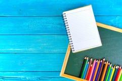 Schließen Sie herauf Anordnung für Bleistiftfarbe, Buch und Kreidebrett auf blauem Hintergrund Stockfoto