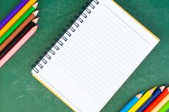 Schließen Sie herauf Anordnung für Bleistiftfarbe, Buch und Kreidebrett auf blauem Hintergrund Stockfotografie