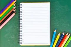 Schließen Sie herauf Anordnung für Bleistiftfarbe, Buch und Kreidebrett auf blauem Hintergrund Lizenzfreie Stockfotos