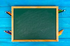 Schließen Sie herauf Anordnung für Bleistiftfarbe und Kreidebrett auf blauem Hintergrund Stockfoto