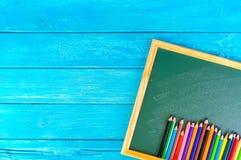 Schließen Sie herauf Anordnung für Bleistiftfarbe und Kreidebrett auf blauem Hintergrund Stockfotos