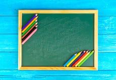 Schließen Sie herauf Anordnung für Bleistiftfarbe und Kreidebrett auf blauem Hintergrund Lizenzfreie Stockfotografie