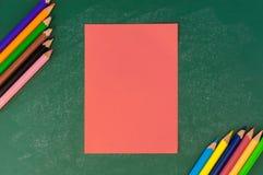 Schließen Sie herauf Anordnung für Papieranmerkungs- und Bleistiftfarbe auf Kreidebrett Stockfotografie
