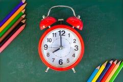 Schließen Sie herauf Anordnung für Uhr- und Bleistiftfarbe auf Kreidebrett Stockbilder